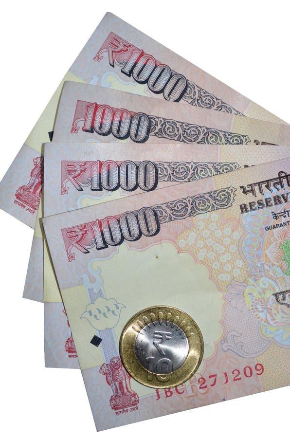 Indiska valutarupieanmärkningar av värde 1000 och myntet royaltyfri bild
