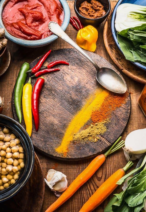 Indiska vegetariska matlagningingredienser med färgrika jordningskryddor, indisk currydeg, fågelungeärtor, grönsaker och sked på  royaltyfri foto