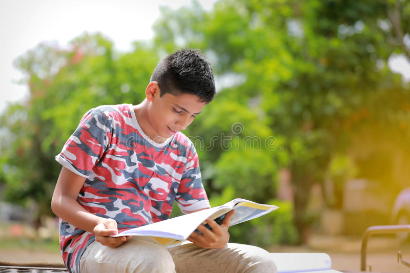 Indiskt barn som läser en bok royaltyfria bilder