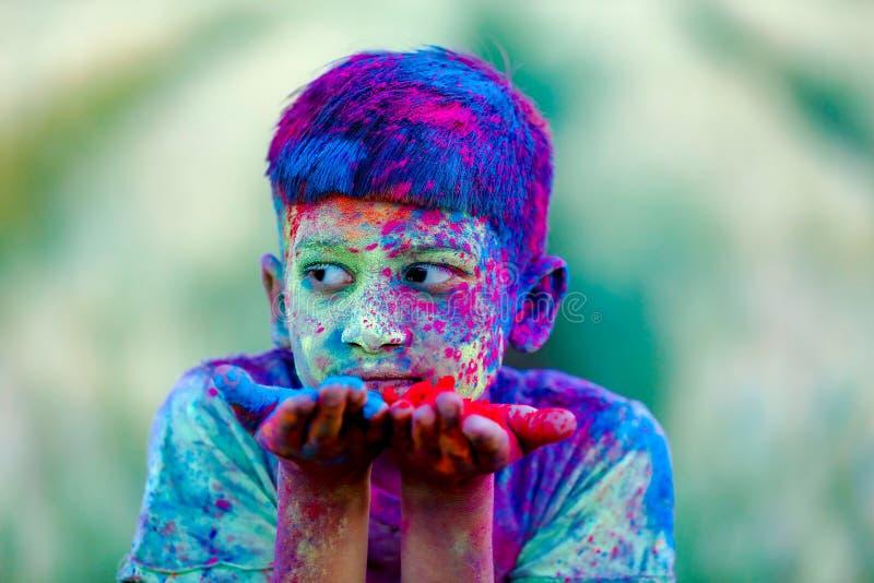 Indiskt barn som spelar med färgen i holifestival fotografering för bildbyråer