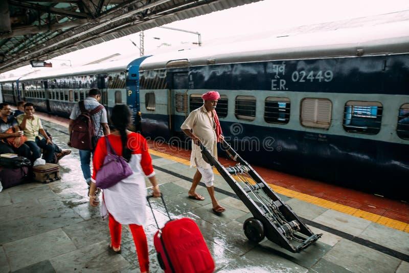 Indiskt folk som går med hans vagn på plattformen för överföring av gods inom Howrah föreningspunktjärnvägsstation i Kolkata, Ind arkivbilder