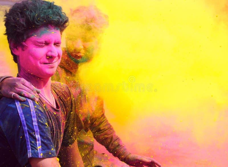 Indiskt folk som spelar med färgrikt gulal på Holi royaltyfria foton