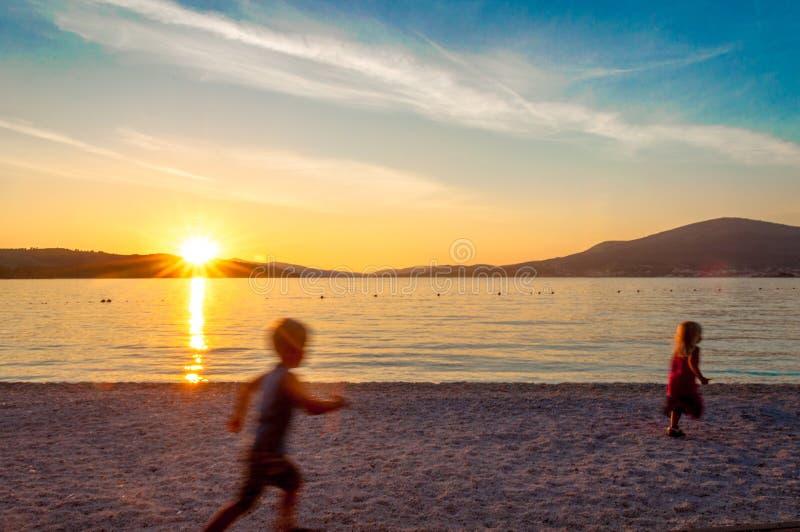 Indistinct small children running on beach at sunset. stock photography