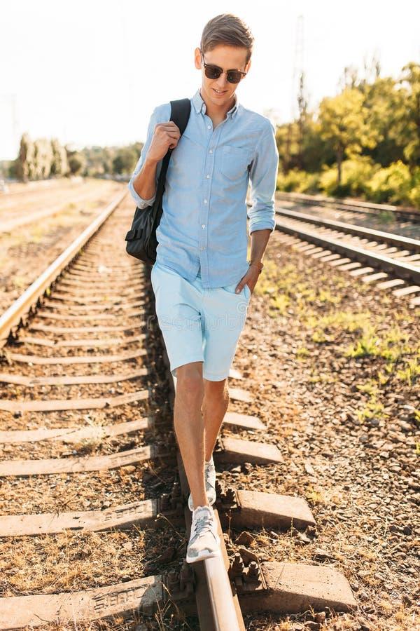 Indivíduo à moda bonito com os vidros, levantando nos trilhos do trem no por do sol, moderno que levanta na roupa à moda, para an foto de stock royalty free