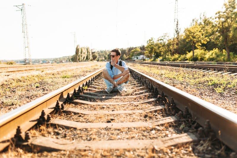 Indivíduo à moda bonito com os vidros, levantando o assento nos trilhos do trem no por do sol, moderno que levanta na roupa à mod fotografia de stock