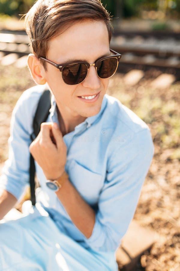 Indivíduo à moda bonito com os vidros, levantando o assento nos trilhos do trem no por do sol, moderno que levanta na roupa à mod imagens de stock