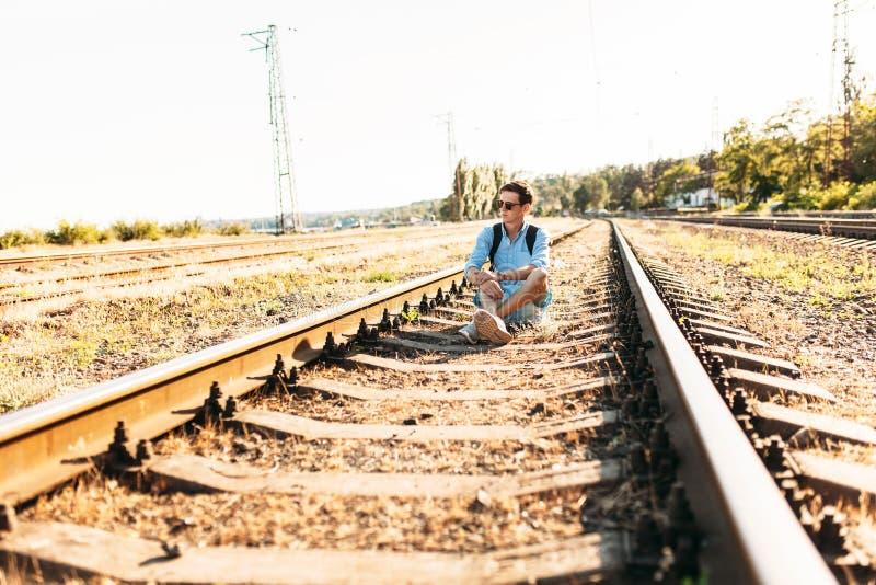 Indivíduo à moda bonito com os vidros, levantando o assento nos trilhos do trem no por do sol, moderno que levanta na roupa à mod imagens de stock royalty free