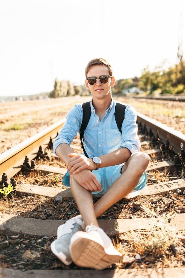 Indivíduo à moda bonito com os vidros, levantando o assento nos trilhos do trem no por do sol, moderno que levanta na roupa à mod imagem de stock royalty free