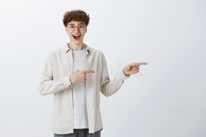 Indivíduo adolescente devista adorável em vidros redondos com cabelo encaracolado que aponta certo com indicador e sorriso fotos de stock