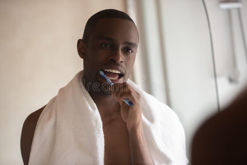 Indivíduo africano após o olhar do chuveiro nos dentes de escovadela do espelho foto de stock royalty free