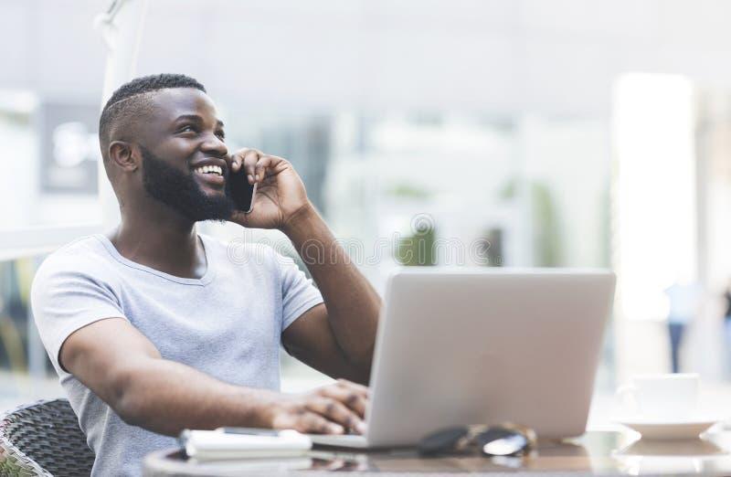 Indivíduo africano considerável novo que trabalha no portátil imagem de stock