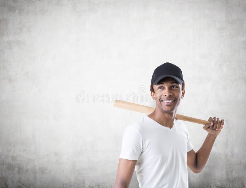 Indivíduo afro-americano de sorriso com um bastão, concreto imagem de stock