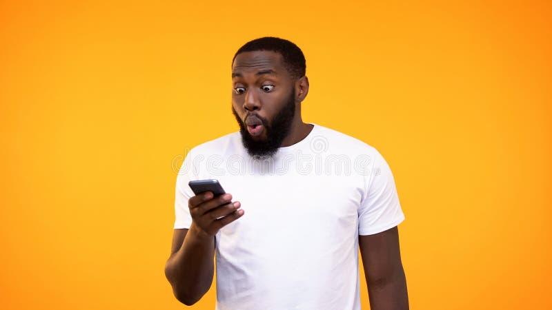 Indivíduo afro-americano surpreendido que olha a tela do telefone, vencedor de loteria, apostando o app fotos de stock