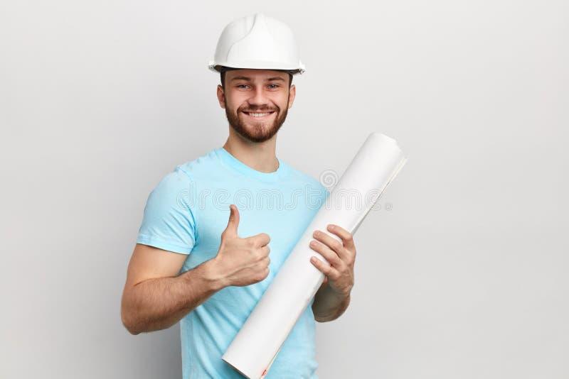 Indivíduo agradável alegre no polegar protetor da exibição do chapéu acima, exultando no modelo fotografia de stock