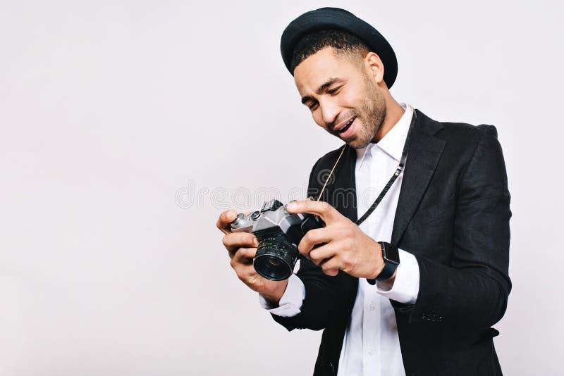 Indivíduo alegre considerável no terno, chapéu que olha a câmera nas mãos no fundo branco Viajando, turista, tendo o divertimento imagem de stock royalty free