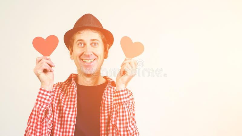 Indivíduo alegre louco funky que guarda corações vermelhos Homem no amor Copie o espaço Homem engraçado na camisa do chapéu negro foto de stock