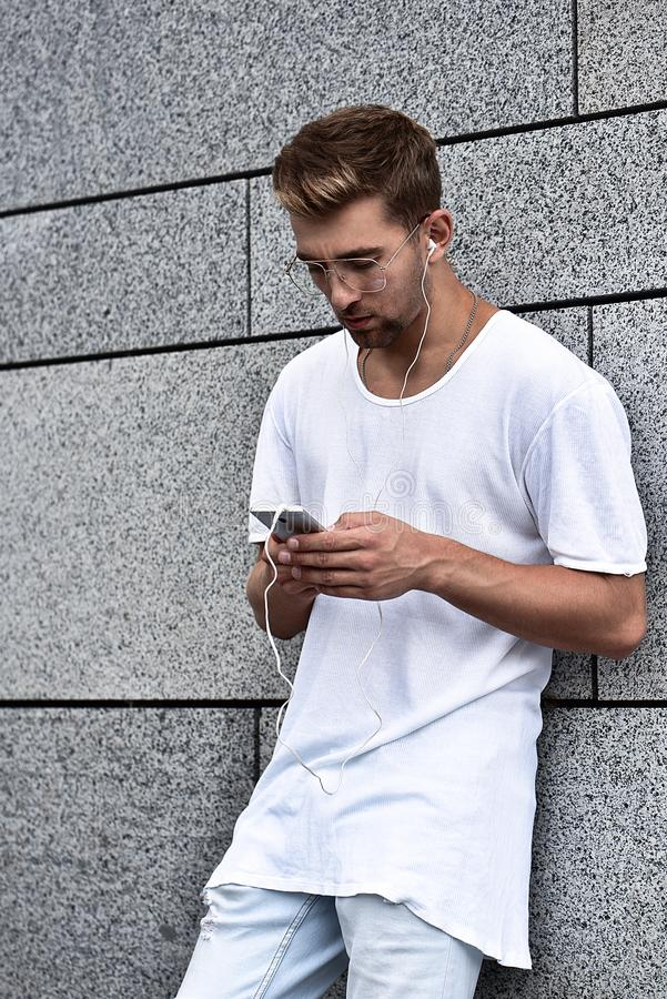 Indivíduo alegre vestido no t-shirt branco na rua, escutando a música com os fones de ouvido, guardando o telefone celular imagens de stock royalty free