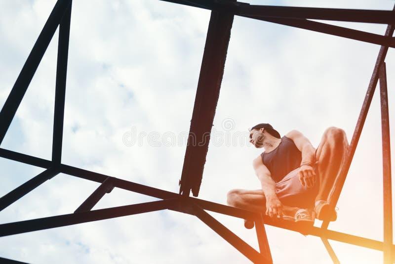 Indivíduo arriscado novo que equilibra e que senta-se na construção do metal alto imagem de stock