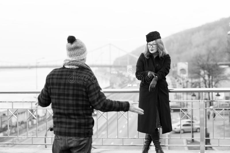 Indivíduo atrasado até agora A mulher mostra épocas no braço O homem espalhou o seu distribui na ponte e na área de passeio fotografia de stock