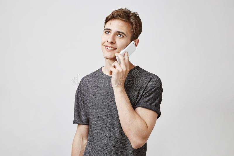Indivíduo atrativo com cabelo marrom em uma camisa cinzenta na moda que está perto da parede branca e que fala no telefone com su imagens de stock royalty free