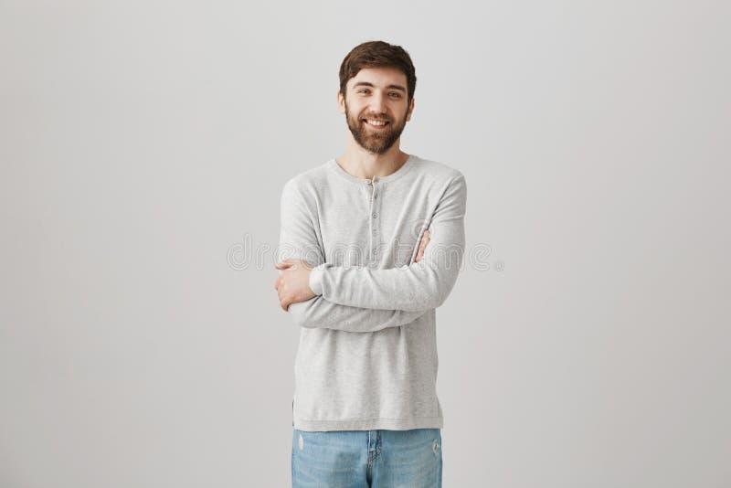 Indivíduo bonito tímido positivo com a barba que está com mãos cruzadas no pulôver sobre o fundo cinzento, sorrindo e fotos de stock royalty free