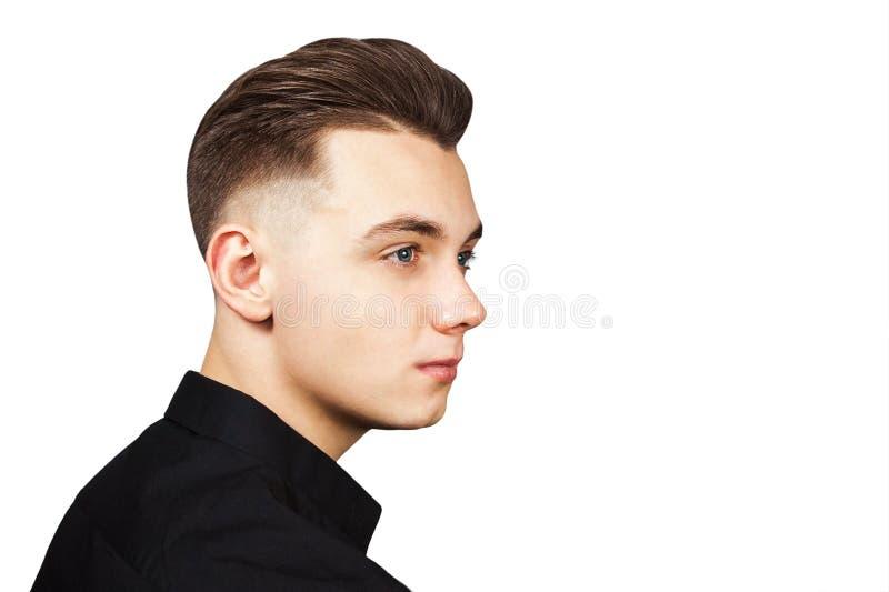 Indivíduo branco novo com um penteado do pompadour vestido na camisa preta com uma cara séria isolada no fundo branco foto de stock