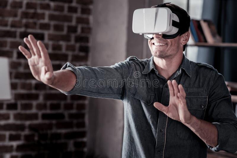Indivíduo brilhante que joga jogos de vídeo ao vestir auriculares do vr imagem de stock royalty free