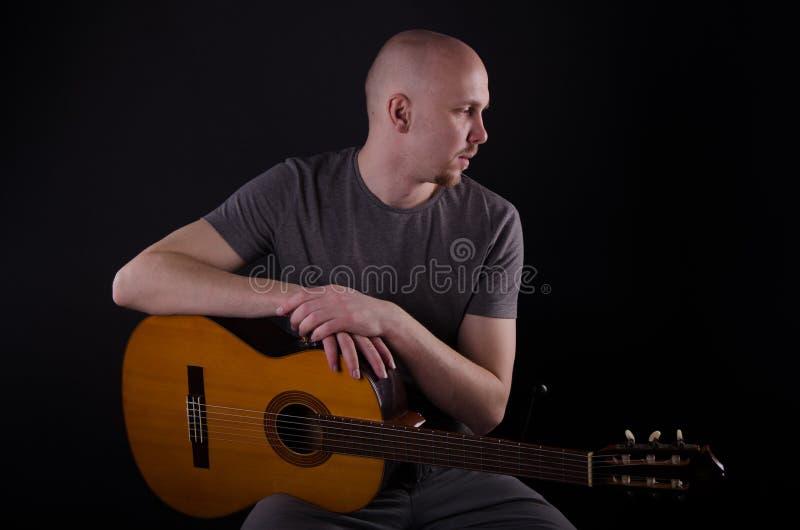 Indivíduo calvo agradável com uma guitarra imagens de stock royalty free