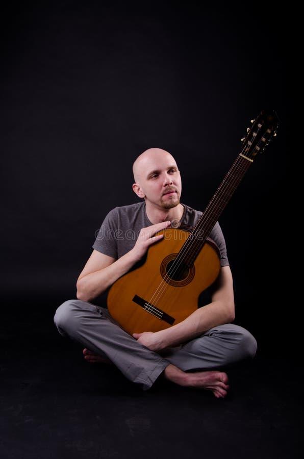 Indivíduo calvo agradável com uma guitarra imagem de stock