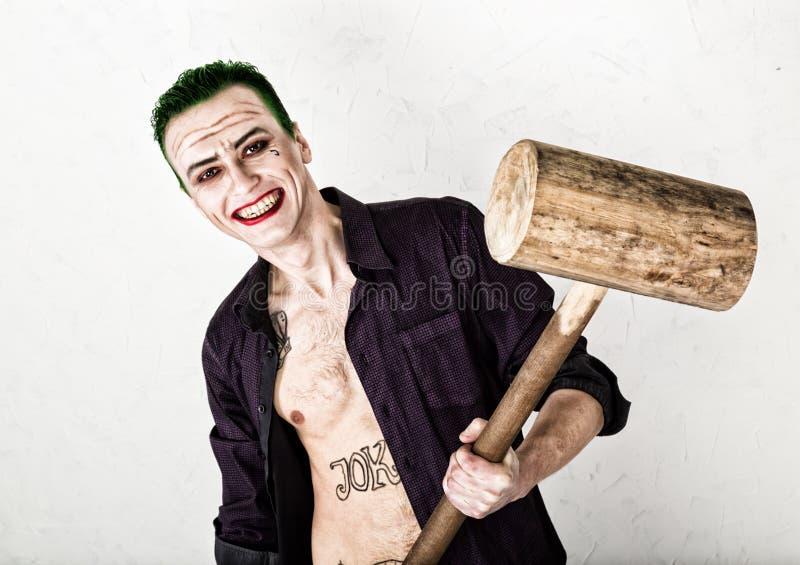 Indivíduo com a cara louca do palhaço, cabelo verde e sorriso idiota traje carnaval guardando o martelo para o grilo imagens de stock royalty free