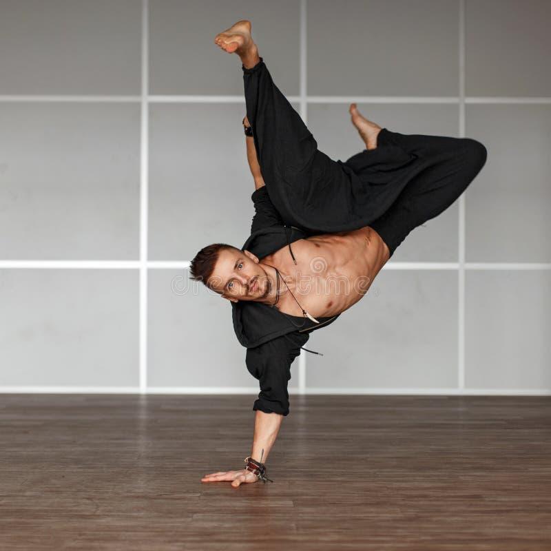 Indivíduo considerável e desportivo consideravelmente novo na roupa preta, dança, dentro imagens de stock