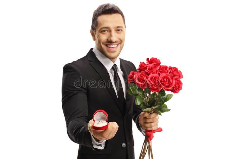 Indivíduo considerável em um terno que guarda um ramalhete das rosas e de um anel em uma caixa fotografia de stock