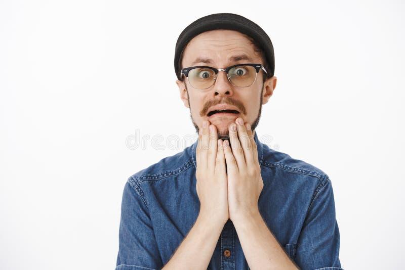 Indivíduo considerável incomodado impossível com a barba no beanie preto e nos vidros que guardam as palmas no queixo que olha de imagem de stock royalty free