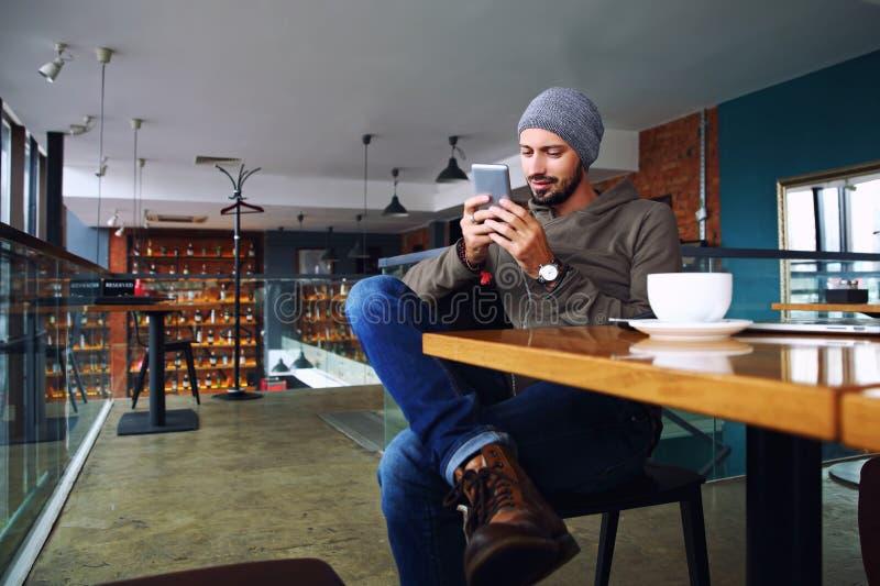Indivíduo considerável novo do moderno com a barba que texting com seu telefone celular na barra e que come um cappuccino foto de stock