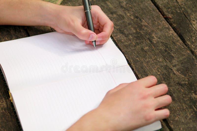 Indivíduo considerável novo que senta-se na tabela de madeira, escrevendo um livro, fazendo trabalhos de casa, tomando notas, apr foto de stock