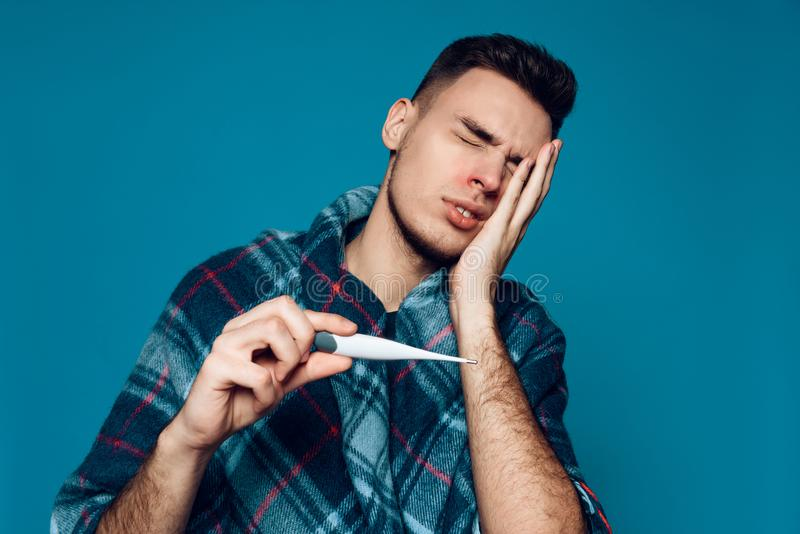 Indivíduo da doença com temperatura de medição do vírus da gripe imagens de stock