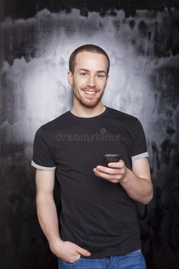 Indivíduo de sorriso com smartphone que datilografa SMS imagem de stock