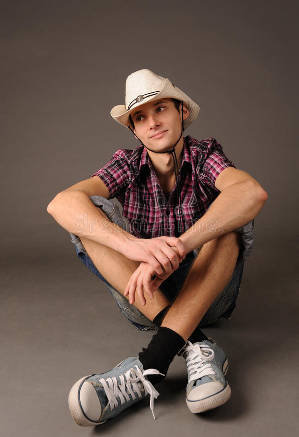 Indivíduo de sorriso nas sapatilhas e no chapéu imagem de stock royalty free