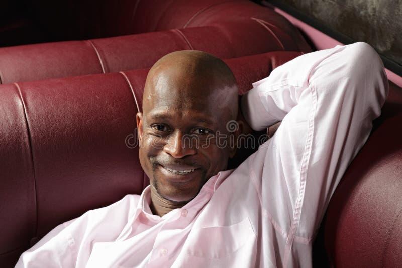 Indivíduo de sorriso no sofá imagens de stock royalty free