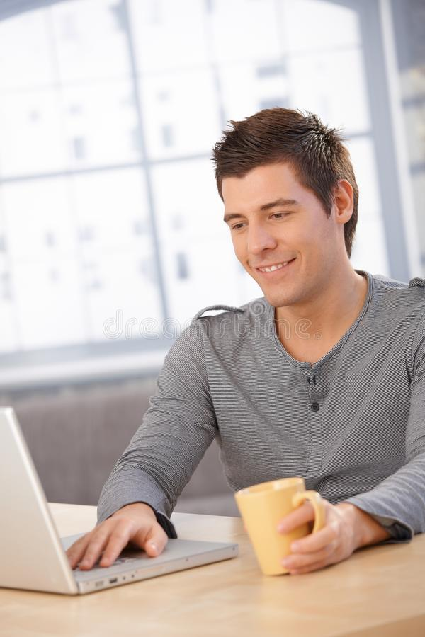 Indivíduo de sorriso que usa o computador portátil fotos de stock royalty free