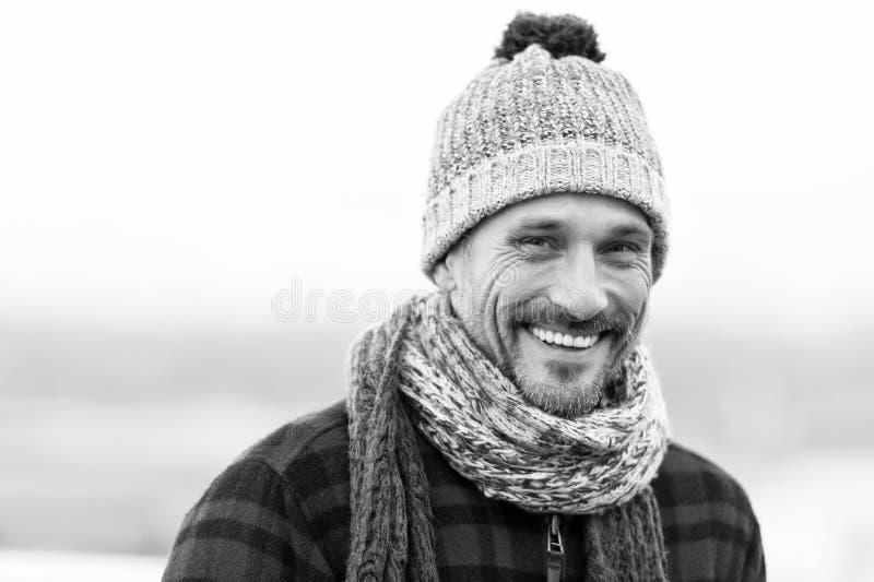 Indivíduo de sorriso urbano Homem feliz no chapéu e no lenço de lã Sorrisos engraçados do homem à câmera Close up da cara urbana  imagem de stock