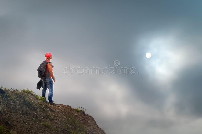 Indivíduo desportivo com uma trouxa na borda do penhasco contra nuvens tormentosos e sol conceito do curso imagens de stock
