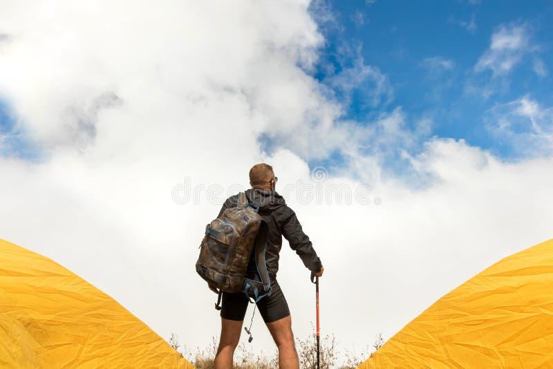 Indivíduo desportivo novo com uma trouxa em um acampamento da barraca que olha longe contra um fundo de nuvens de cúmulo e de um  fotos de stock