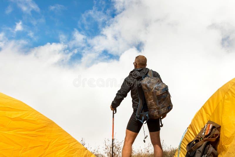 Indivíduo desportivo novo com uma trouxa em um acampamento da barraca que olha longe contra um fundo de nuvens de cúmulo e de um  imagem de stock