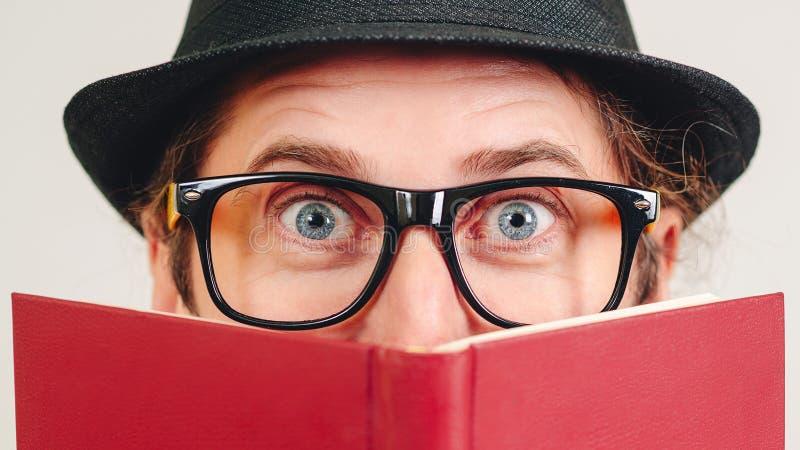 Indivíduo do lerdo nos vidros que escondem atrás do livro Amante de livro O homem excitado nos vidros tem a grande ideia Conceito fotografia de stock