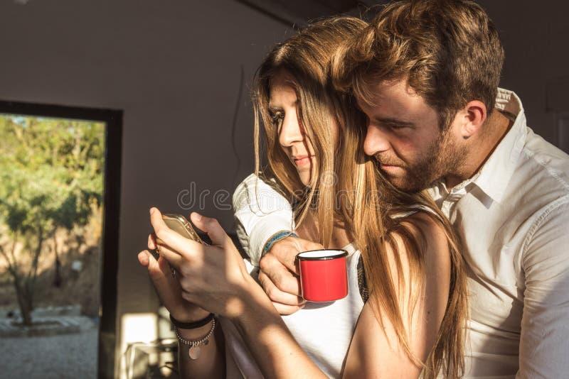 Indivíduo e menina que olham seus telefones celulares em casa Pares de indivíduo e de menina que olham seu telefone celular fotografia de stock royalty free