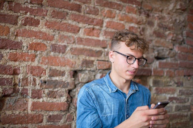 Indivíduo elegante do moderno que conversa na rede social através do telefone celular, sentando-se contra a parede com espaço da  fotografia de stock royalty free