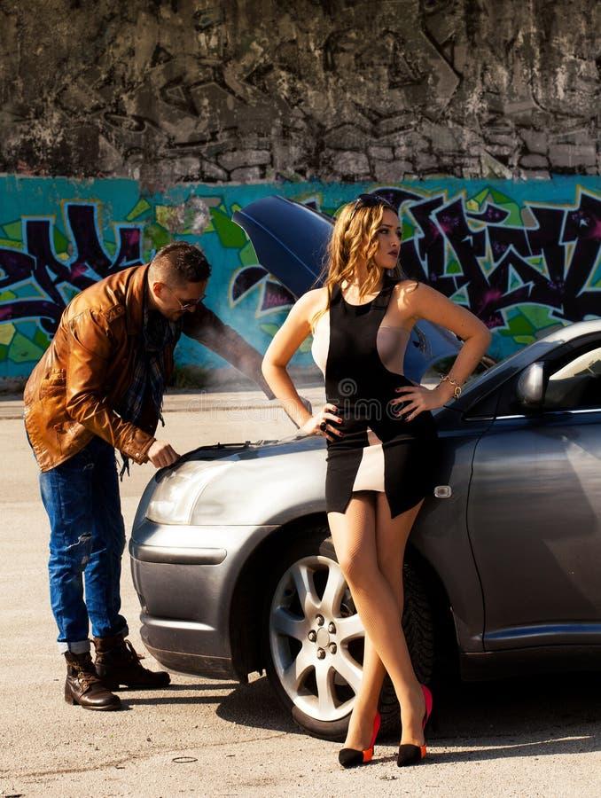 Indivíduo elegante que repara um carro próximo que esteja a menina impressionante imagem de stock