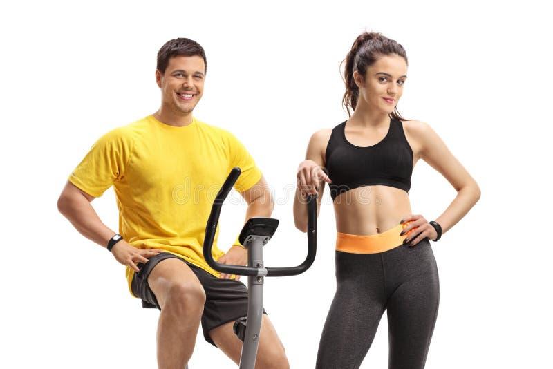 Indivíduo em uma bicicleta de exercício com uma jovem mulher no portswear imagem de stock royalty free