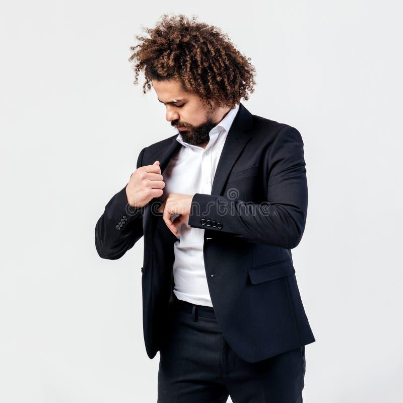 Indivíduo encaracolado moreno à moda vestido em um terno preto clássico e em umas poses brancas da camisa no estúdio no branco imagens de stock